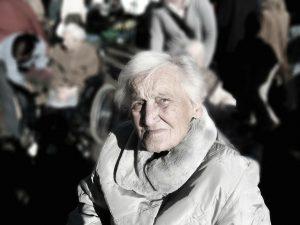 oudere vrouw met winterjas kijkt in de camera
