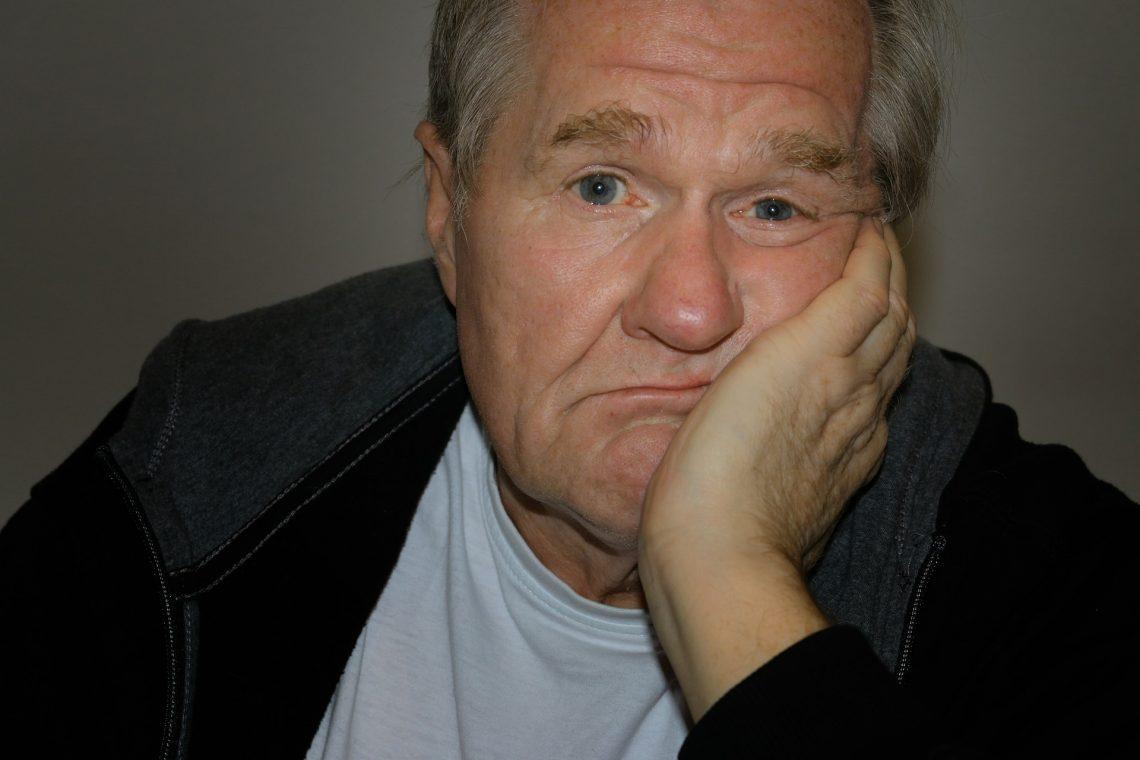 oudere lusteloze mandie voor zich uitkijkt met hoofd n zijn hand