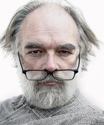 eigenzinnige oude man met grijze baard en bril op zijn bovenlip