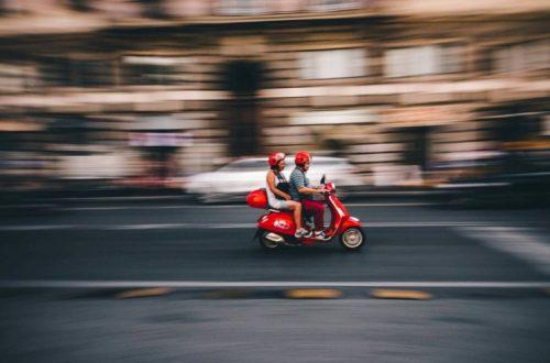 ouder echtpaar op rode scooter op werelreis