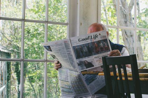 Oudere man leest rustig het nieuws in de krant